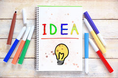 Some markers on a white wooden desktop and a notebook with the word IDEA colorful hand written on it. Empty copy space. For Editor`s text stock photography