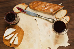 Some meal with red wine, bread, jam and cheese on oldened paper. Lunch or breakfast with a glass of red wine, fresh baguette bread, brie or camembert cheese and royalty free stock photography