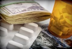 Some medicines next to a block of tickets of dollar, conceptual. Image Stock Photography