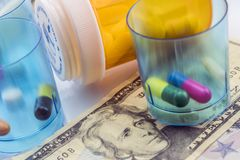 Some medicines next to a block of tickets of dollar,. Conceptual image royalty free stock images