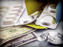 Some medicines next to a block of tickets of dollar,. Conceptual image Royalty Free Stock Image
