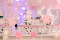 SOME MEMORIES IN A BABYGIRL SHOWER. A special babyshower with many sourveniers and beautiful details on the table  and in the background there are many sweets Royalty Free Stock Image