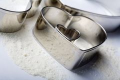 Some metal heart-cookie-cutter. S with some flour on white background. Tilt view stock images