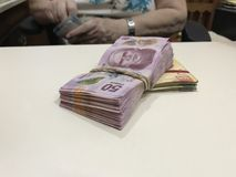 Some mexican peso money bills stacked on a beige coloured table royalty free stock images