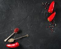 Some mini peppers, dry spices and salt over black background. Copy space royalty free stock images