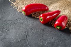 Some mini peppers on a sack over black background. Copy space royalty free stock photo