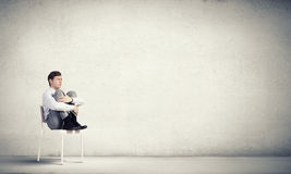 Some minutes of isolation!. Young businessman sitting in chair and relaxing stock image