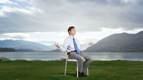 Some minutes of isolation!. Young businessman sitting in chair and relaxing stock photography
