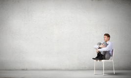 Some minutes of isolation!. Young businessman sitting in chair and relaxing stock images