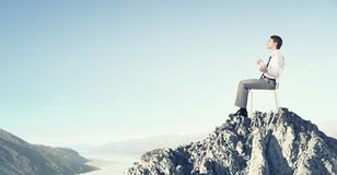 Some minutes of isolation!. Young businessman sitting on top of mountain and relaxing royalty free stock photo