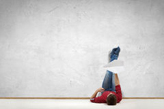 Some minutes of relaxation. Young man lying on floor with legs raised up on wall Royalty Free Stock Images