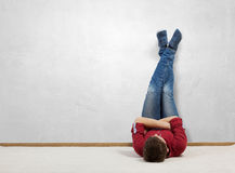 Some minutes of relaxation. Young man lying on floor with legs raised up on wall Royalty Free Stock Photos