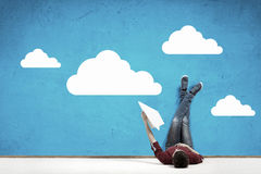 Some minutes of relaxation. Young man lying on floor with legs raised up on wall Stock Images