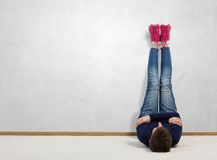 Some minutes of relaxation. Young woman lying on floor with legs raised up Royalty Free Stock Image