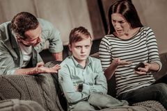 Emotional woman trying to understand her son. Some misunderstandings. Serious boy wrinkling forehead while looking straight at camera royalty free stock images
