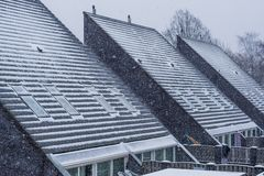 Modern pointed rooftops covered in snow, snowy and cold weather in winter season, new dutch house architecture stock photos
