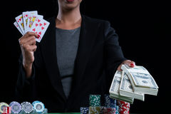 Some money and hearts suit straight flush in female hands. Selective focus at some money and gearts suit straight flush, poker card in female hands with stack of Royalty Free Stock Photo