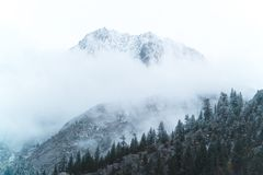 Some moody clouds fog the peak. Of a snow covered mountain in California`s Sierra Nevada near June Lake stock images
