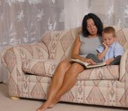 Some More Reading. Mother and son reading a book royalty free stock images