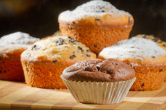 Some muffins with caster sugar. On black background royalty free stock image