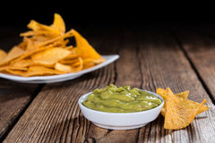 Some Nachos (with Guacamole) on wood. En background (close-up shot Royalty Free Stock Image