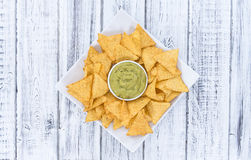 Some Nachos (with Guacamole) on wood. En background (close-up shot Stock Photography