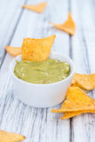 Some Nachos (with Guacamole) on wood. En background (close-up shot Royalty Free Stock Photo