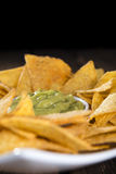 Some Nachos (with Guacamole) on wood. En background (close-up shot Stock Photo