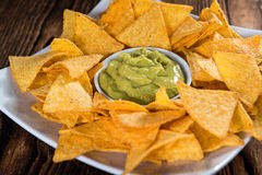 Some Nachos (with Guacamole) on wood. En background (close-up shot Stock Images