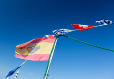Some national flags fluttering against the blue sky Stock Photos