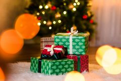 Some nice presents in a new year wrapping paper. On a furry white carpet, beautiful christmas tree on the background. Christmastime celebration, home decorated royalty free stock images
