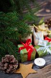 Some nice presents in a new year wrapping paper on wooden table, beautiful christmas tree on the background. Christmastime celebration, home decorated stock images