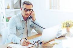Some notes for the day. Handsome mature man talking on phone and making some notes while sitting at his working place royalty free stock image