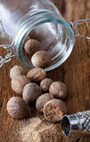 Some nutmeg in a glass. Some Nutmegs are in a glass and some are outside, a grated nutmeg and nutmeg-grater lying on rustic wooden background Royalty Free Stock Image