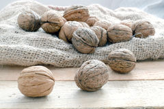 Some nuts scattered on a sack. On a rustic wooden kitchen, top view Stock Photo