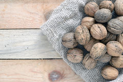 Some nuts scattered on a sack. On a rustic wooden kitchen, top view Stock Images