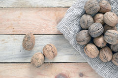 Some nuts scattered on a sack on a wooden table. Some nuts scattered on a rustic wooden table of a rustic kitchen, macro Royalty Free Stock Photos
