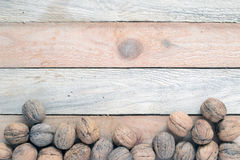 Some nuts scattered on a WOODEN TABLE. Some nuts scattered on a rustic wooden table of a rustic kitchen, macro Stock Image