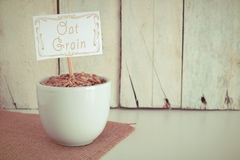 Some oat grain in a bowl in the herbalist's. Empty copy space against a wooden background Royalty Free Stock Photo