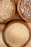 Some oatmeal, millet, rice are in woody bowls. It is close up Stock Images