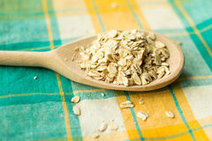 Some oatmeal in the wooden spoon. The most useful food for breakfast Royalty Free Stock Images