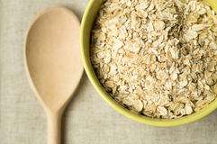 Some oatmeal in the wooden spoon. The most useful food for breakfast Royalty Free Stock Photo