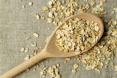 Some oatmeal in the wooden spoon. The most useful food for breakfast Stock Photos