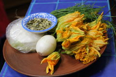 Some Oaxacan Cooking Ingredients. Zucchini blossoms, cheese, pumpkin seeds, onion, and some herbs on a blue counter Royalty Free Stock Images