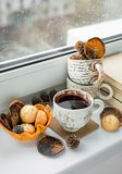 Autumn mood card. Black coffee on the window at rainy weather. B. Some old books, a cup of black coffee. Rainy day. Dried orange and cones stock image