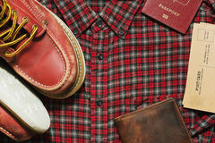 Some old-fashioned travel equipment. Old worn boots, leather wallet, vintage postcards and a passport on the checkered shirt Royalty Free Stock Photo