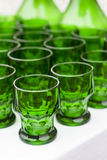 Some old green glasses. Set of green drinking glasses on white table royalty free stock photo