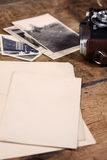Some old photos and vintage camera on wooden table Stock Images