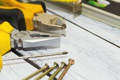 Work tools on wooden desk. Some old and plently ised tools lie on rough wooden desk. Handyman working space. Honest labor concept. Close-up capture, selective stock photo