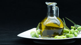 Some olives and a jar full of oil and a branch of olive tree on. A white dish on a black background stock image